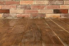Brown wooden floor with brick wall background with copy space royalty free stock photo