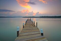 Brown Wooden Footbridge on Body of Water during Sunrise Royalty Free Stock Photo