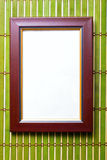 Brown wooden frame. Over bamboo mat Royalty Free Stock Photo