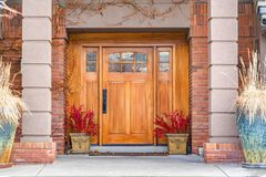 Brown wooden front door with decorative glass panels at the entrance of a home. The doorway is framed with red brick wall, brown vines, and potted plants royalty free stock images