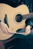 Brown Wooden Guitar in Front of Smartphone Royalty Free Stock Images