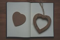 Brown Wooden Heart Shape Pendant on White Book Royalty Free Stock Photos