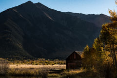 Brown Wooden House Across Mountain during Daylight Royalty Free Stock Photos