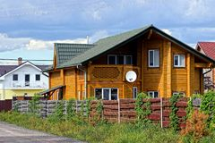 Brown wooden house behind a planted fence Stock Photography