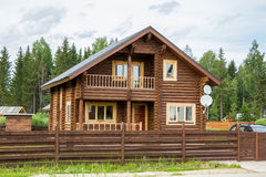 Brown wooden house behind wooden fence Stock Image