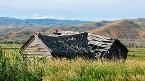 Brown Wooden House on Field Near Mountain during Daytime Royalty Free Stock Photos