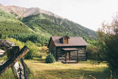 Brown Wooden House Surrounded By Green Grass and Trees Near Mountain Royalty Free Stock Photography