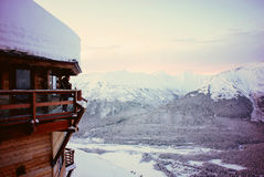 Brown Wooden House Surrounded by Mountains and Snow during Winter Royalty Free Stock Images