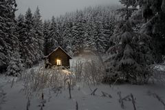 Brown Wooden House on White Snow Filed Forest With Trees Royalty Free Stock Photos