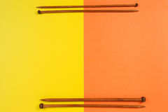 Brown wooden knitting needles arranged as frame border on yellow and orange background Royalty Free Stock Photos