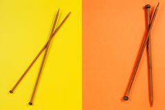 Brown wooden knitting needles on yellow and orange background Stock Photos