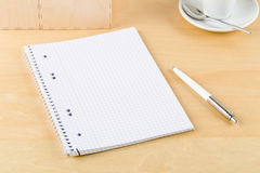 Brown wooden office desk with empty notepad, pen and cup Royalty Free Stock Photo