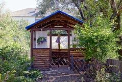 Brown wooden outdoor gazebo in the green garden Stock Photography