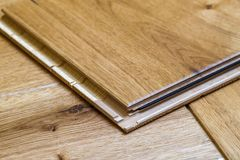 Brown wooden parquet floor planks installation , close up. Carpentry concept. stock photos