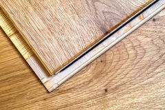 Brown wooden parquet floor planks installation , close up. Carpentry concept. stock photography
