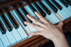 Brown Wooden Piano Used by a Person Using 2 Fingers Royalty Free Stock Image