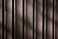 Brown wooden planks background. Closeup of wooden planks illuminated with sun, with sensitive shadows stock image