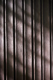 Brown wooden planks background. Closeup of wooden planks illuminated with sun, with sensitive shadows royalty free stock images
