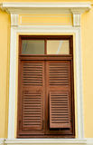 Brown wooden shutters on the yellow wall. Show home concept Stock Photography