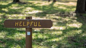 Brown wooden sign in grassy field with helpful written on it stock image