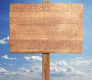 Brown wooden signpost against blue sky. Royalty Free Stock Photography
