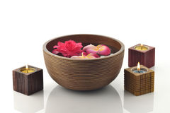 Brown Wooden Spa Bowl on White Background with Candles and Flowers Royalty Free Stock Photos