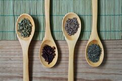 Brown Wooden Spoon With Herbs on Top of Green Bamboo Mat and Brown Wooden Surface Stock Image