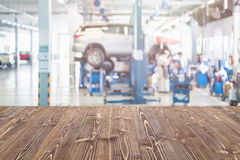 Brown wooden table free space and blurred background of car tech. Empty brown wooden table free space and blurred background of car technician repairing the car stock image