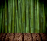 Brown wooden table on the green bamboo forest blur background. Royalty Free Stock Photography