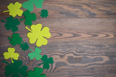 Brown wooden table with handmade green leaves of clover. Brown wooden table with green leaves of clover. Place for your text. Background to St. Patrick`s Day Royalty Free Stock Image