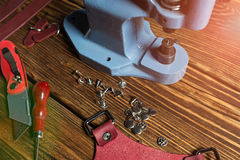 On a brown wooden table is a press, tools and accessories for working with leather. Stock Photo