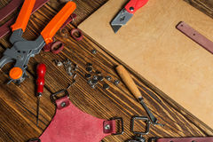 On brown wooden table scattered with tools and accessories for working with leather. Stock Photography