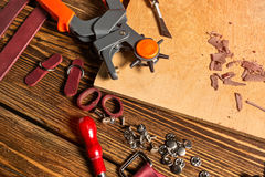 On brown wooden table scattered with tools and accessories for working with leather. Stock Images