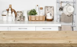 Brown wooden texture table over blurred image of kitchen bench.  Stock Photos