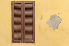 Brown wooden texture window frame on a yellow old cement house royalty free stock images