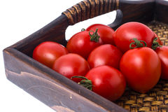 Brown wooden tray with small red tomatoes. Studio Photor Stock Images
