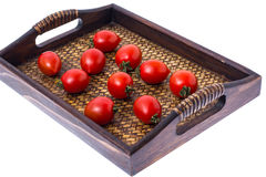 Brown wooden tray with small red tomatoes. Studio Photor Stock Image