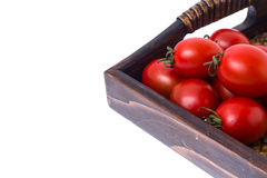 Brown wooden tray with small red tomatoes. Studio Photor Royalty Free Stock Image