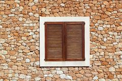 Brown wooden window in masonry wall Royalty Free Stock Photo