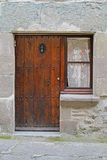 Brown wooden window with white curtain and door with door knocker in Rupit Royalty Free Stock Photo