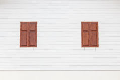 Brown wooden windows on white wooden house. Two brown wooden windows on white wooden house stock photo