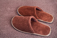Brown wool slipper on mat Stock Images