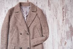 Brown woolen coat, wooden background. Fashion concept. Brown woolen coat, wooden background. Fashion concept Stock Images