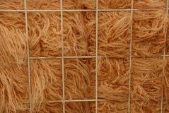 Brown woolen fabric behind a metal lattice royalty free stock photos