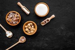 Brown y azúcar blanco en cuencos, cucharada y cuchara El bastón, refind, granuló, los cubos, caramelo Copia negra de la opinión s foto de archivo