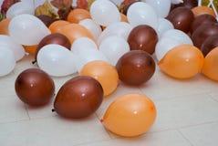 Brown y el color blanco anaranjado de la American National Standard van de fiesta los globos en el piso imagen de archivo