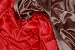 Brown y el paño de seda rojo del satén de dobleces ondulados texturizan el fondo Foto de archivo