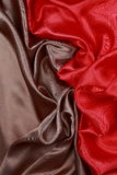 Brown y el paño de seda rojo del satén de dobleces ondulados texturizan el fondo Imagen de archivo