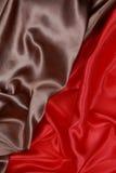 Brown y el paño de seda rojo del satén de dobleces ondulados texturizan el fondo Fotos de archivo