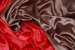 Brown y el paño de seda rojo del satén de dobleces ondulados texturizan el fondo Fotografía de archivo